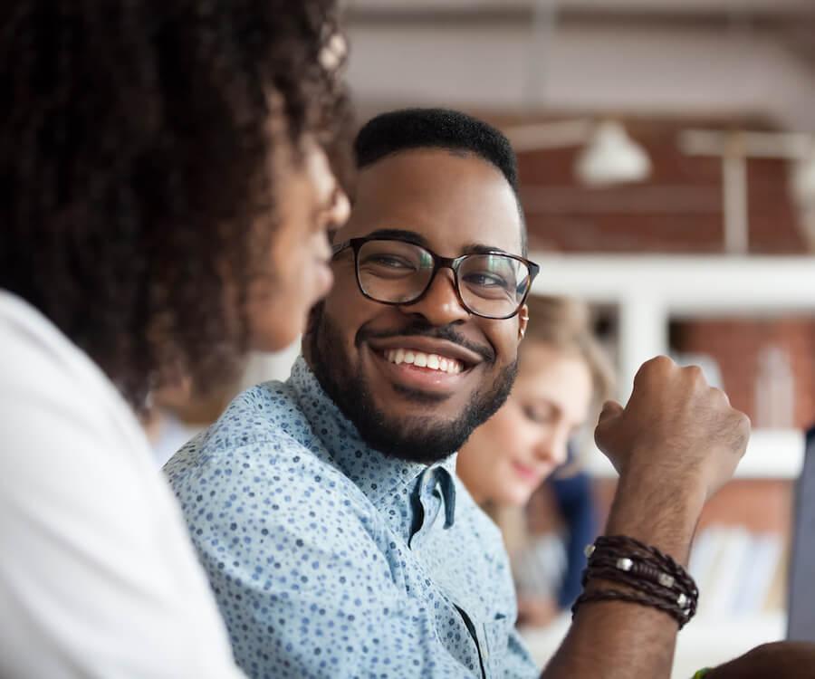 Un homme en chemise sourit à une femme. Ils s'agit de deux personnes heureuses dans un café.