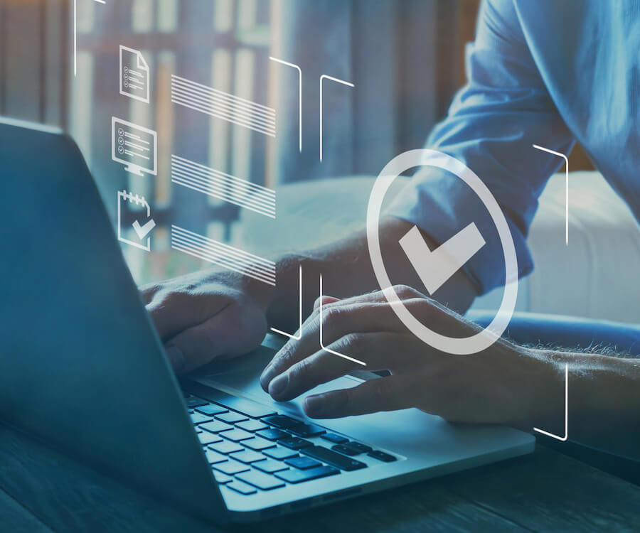 Un homme en chemise bleue utilisant un logiciel de gestion avec des diagrammes blancs volant au-dessus d'un écran d'ordinateur portable.